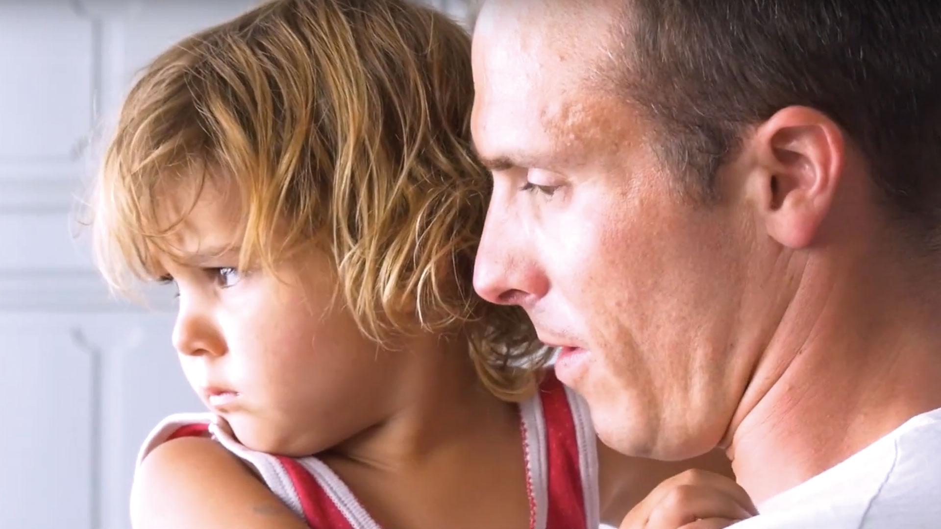 homme portant son fils dans les bras